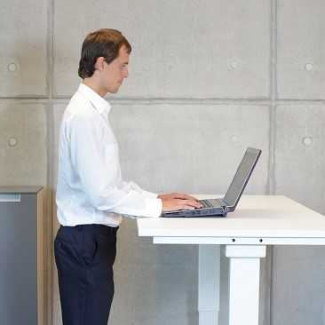 business man in white shirt standing at electrically controlled height adjustment table - full extended - working with laptop