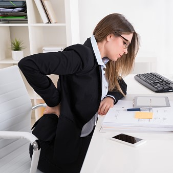 Businesswoman With Backpain Sitting On Chair